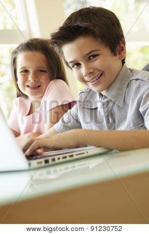 Hispanic Boy And Girl Using Laptop
