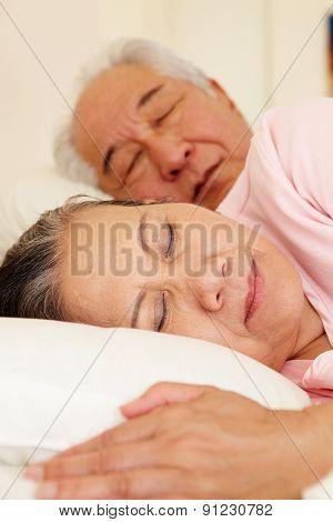 Senior Taiwanese couple sleeping