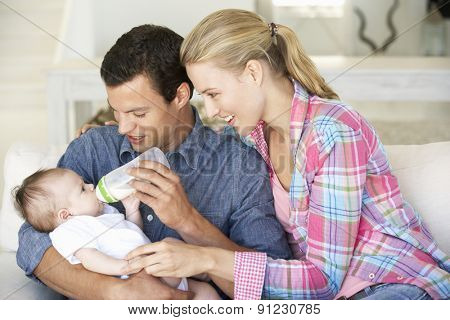 Young Family With Baby Feeding On Sofa At Home