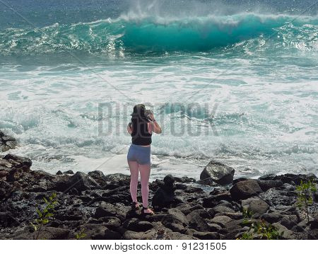 Holiday makers taking photographs of waves.