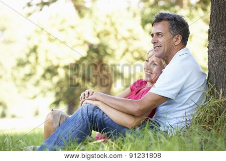 Middle Aged Couple Relaxing In Countryside Leaning Against Tree