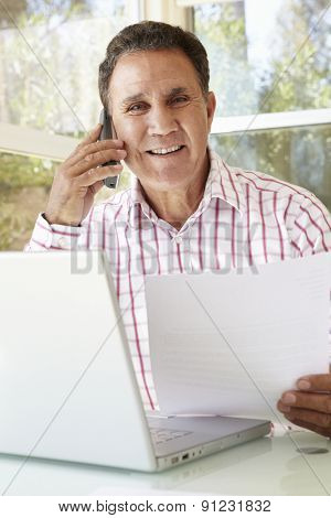 Senior Hispanic Man Working In Home Office