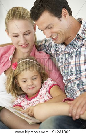 Parents Reading With Daughter At Home
