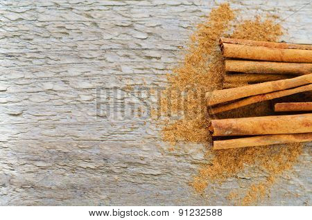 Sticks and powder of cinnamon on wooden table