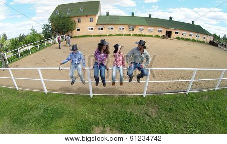Four members family sit on fence near stable of ranch at summer sunny day. Aerial view