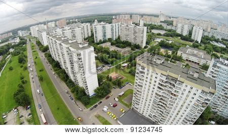 Car traffic near residential houses at summer cloudy day. Aerial view
