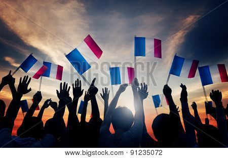 Group of People Waving French Flags in Back Lit Concept