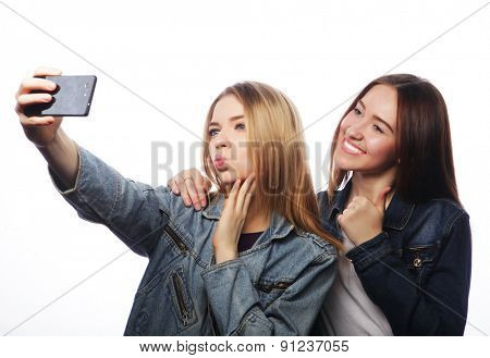technology, friendship and people concept - two smiling teenagers taking picture with smartphone camera