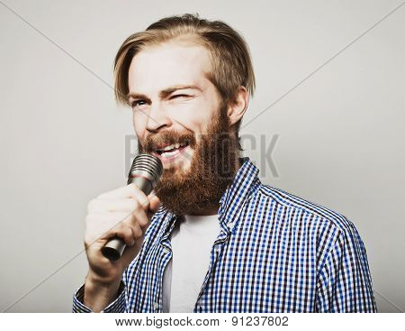 Life style concept: a young man with a beard wearing a white shirt holding a microphone and singing. Over gray background. Special Fashionable toning photos.