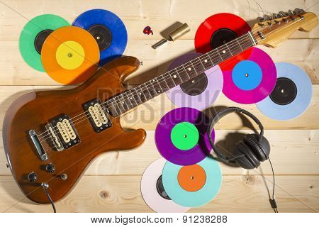 Electric guitar, 33 and 45 vinyl records, and headphones