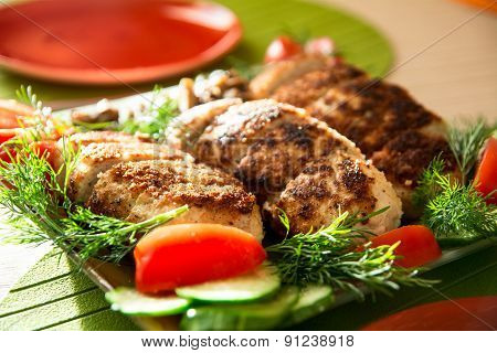 Breading Chicken Cutlets On A Plate With Dill Tomatoes And Cucumbers