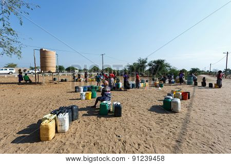 Unidentified Namibian Woman With Child Near Public Tank With Drinking Water.