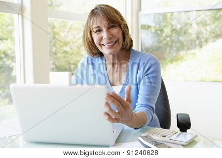 Senior Hispanic Woman Using Laptop In Home Office