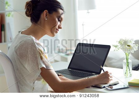 Pretty Young Woman Using Her Laptop In The Office.