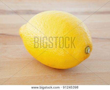 Photo of a yellow lemon on a wooden table