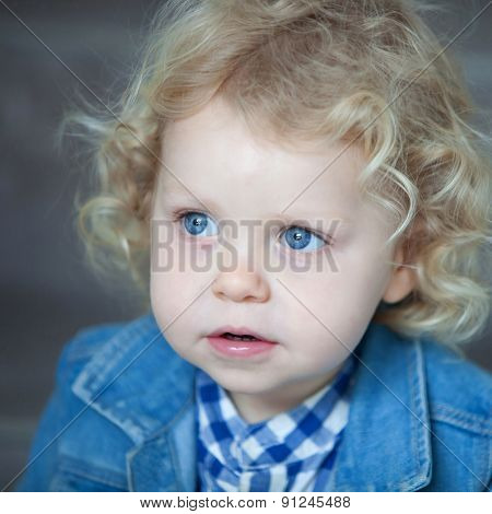 Nice blond baby with blue eyes and curly hair