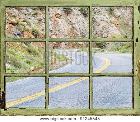 travel concept - a view of windy mountain road  through vintage, grunge, sash window with dirty glass