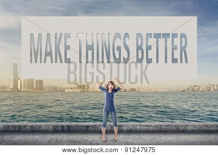 Make things better, words on blank board hold by a young girl in the outdoor.