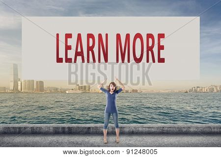 Learn more, words on blank board hold by a young girl in the outdoor.