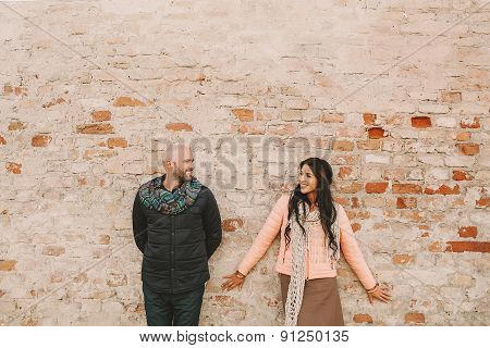 Young Couple Posing Near The Brick Wall In The City