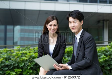 Happy businesswoman and man hold with laptop computer at outdoor