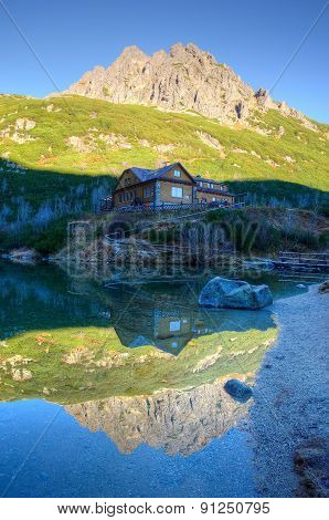 Mountain chalet reflected in the lake.