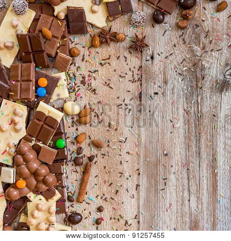 chocolate and candies on a wooden background with space for text