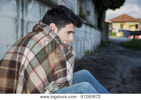 Young male beggar on city sidewalk