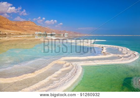 Israeli coast of the Dead Sea. The path from salt picturesquely curls in salty water. Hotels are reflected in smooth water ashore