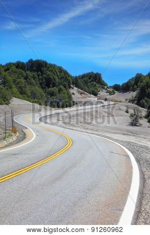 Winding road in Chilean Patagonia, covered remnants of volcanic dust