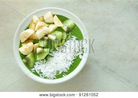 Green smoothie bowl on a white marble background