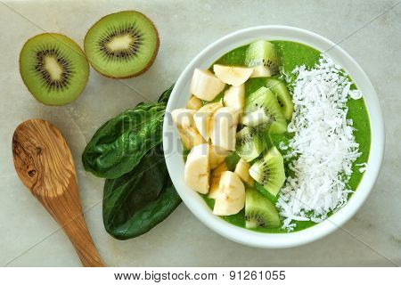 Green smoothie bowl with spoon on white marble