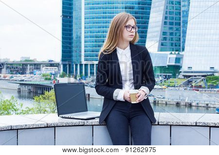 The girl on coffee break with a laptop sitting on the street