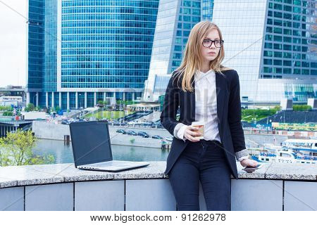 Business woman on coffee break with a laptop sitting on the street