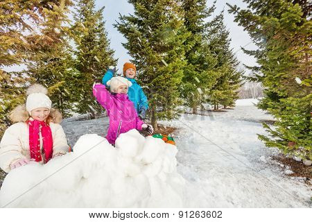 Girls and boy playing snowballs game fight