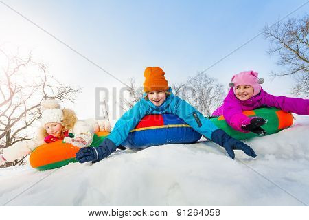 Group of children sliding on the colorful tubes