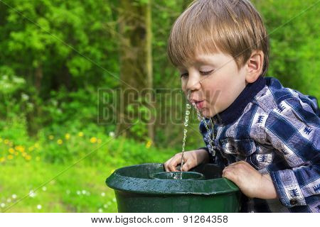 Cute Child Drinking From A Fountain