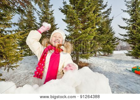 Laughing girl ready to throw snowball in forest