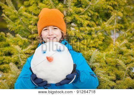 Boy in blue winter jacket holding snowman's head