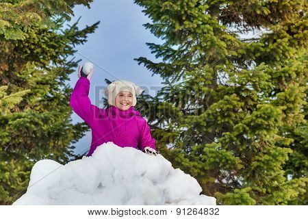 Beautiful girl holds snowball behind snow wall
