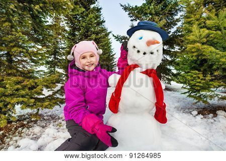 Beautiful girl and cute snowman with red scarf