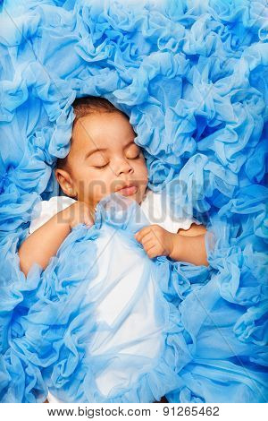 African baby laying and sleeping on the blue cloth