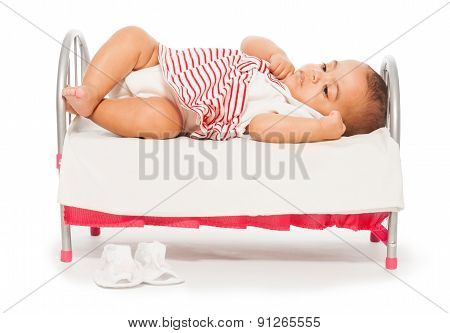 African baby in striped dress on the small bed