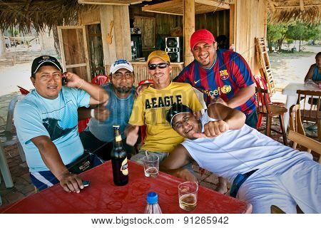 Group of male friends drinking beer in a bungalow by the beach, Puerto Lopez