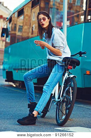 Colorful outdoor portrait of young pretty fashion model with bike. Young blonde sexy woman posing in