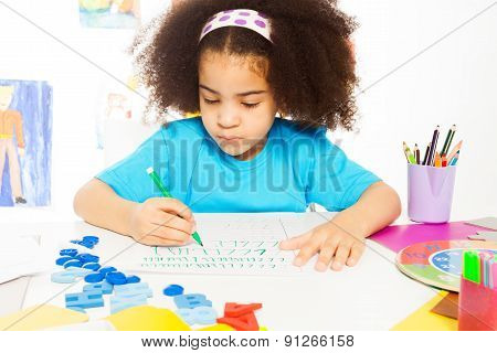 One African girl writing letters with pencil