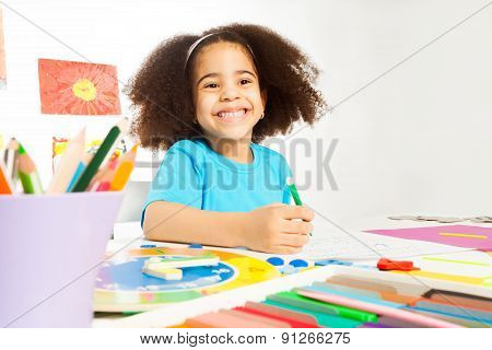 Happy African girl holds pencil writing letters