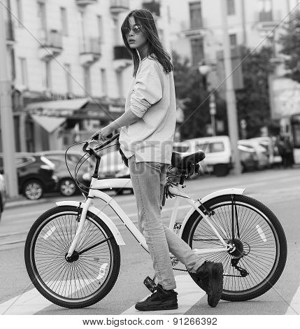 beautiful young hipster woman with bike in the city