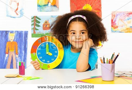 Small African girl holding showing time