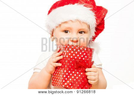 Looking baby in red Christmas hat with gift box